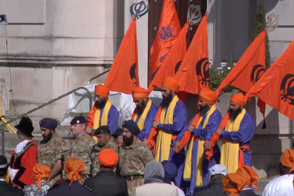 Part of the procession wearing traditional orange headgear